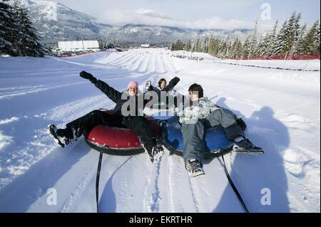 Family fun at the Blackcomb Mountain tube park; Whistler, British Columbia, Canada - Stock Photo