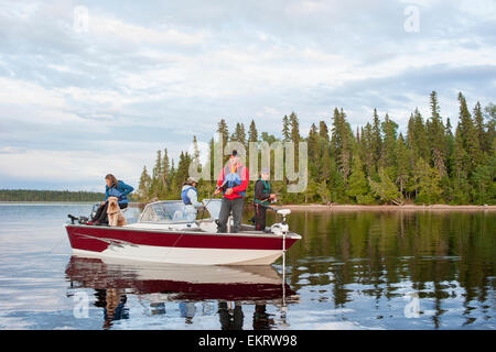 A family fishing from their motorboat on a calm lake in Northern Ontario; Ontario, Canada - Stock Photo