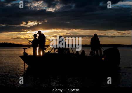 Silhouette of a family fishing from their motorboat on a lake at sunset in Northern Ontario; Ontario, Canada - Stock Photo