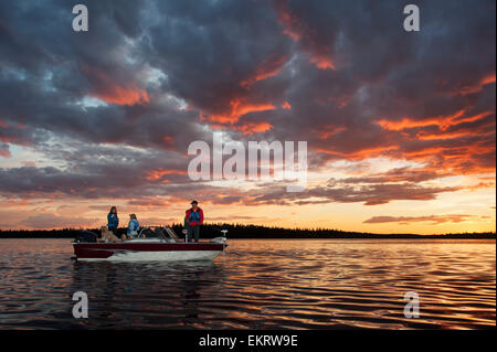 A family fishing from their motorboat on a calm lake at sunset in Northern Ontario; Ontario, Canada - Stock Photo