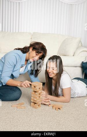 Two Girls Playing A Stacking Block Game - Stock Photo