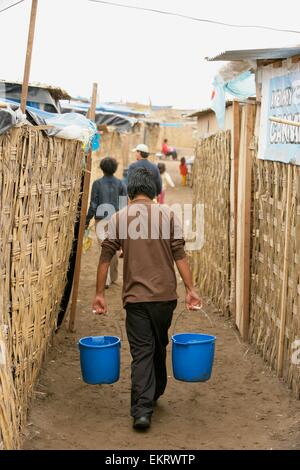 Boy Carrying Pails Down Alleyway, Lima, Peru - Stock Photo