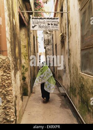 Woman Between Two Buildings; Kenya, Africa - Stock Photo