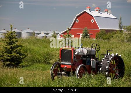 Old Red Tractor In A Field With A Red Barn In The Background; Alberta, Canada - Stock Photo