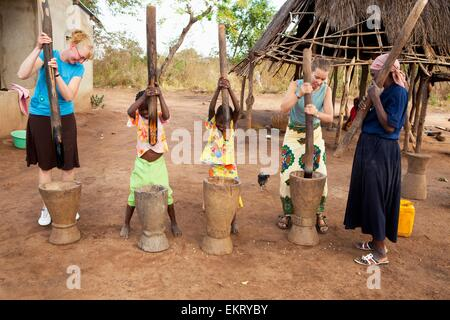 Young Women And Children Pounding Corn Into Flour By Hand; Manica, Mozambique, Africa - Stock Photo