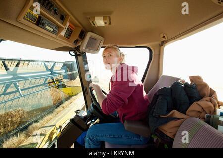 Female Farmer In Cab Of Combine; Three Hills, Alberta, Canada - Stock Photo