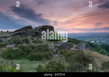 Bright, colourful, orange, red sky at sunset over boulders on a rocky outcrop overlooking Wharfedale - (Otley Chevin, - Stock Photo