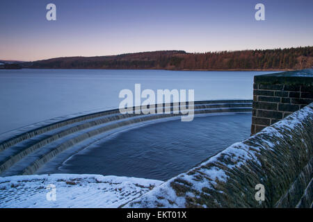 Blue sky at winter sunset over woodland, snow, expanse of water (calm & flowing) & overflow steps - Fewston reservoir, North Yorkshire, England, UK.