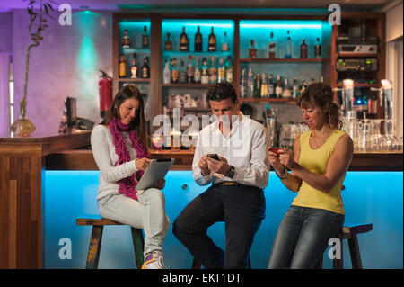 Three People Sitting At The Bar In Republica Cafe Using Their Technology; Tarifa Cadiz Andalusia Spain - Stock Photo