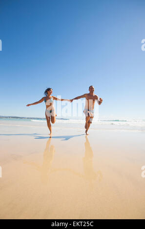 A Couple Holding Hands And Running Down The Beach Together; Gold Coast Queensland Australia - Stock Photo