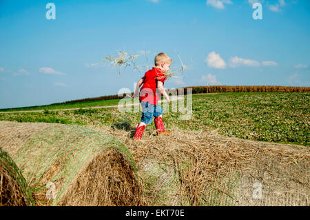 Boy walking on haybales - Stock Photo