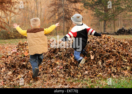 Two boys jump in Fall leaf pile - Stock Photo