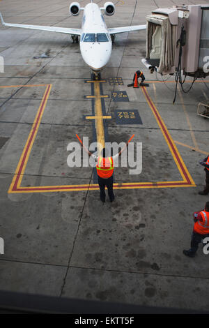 Airport worker guiding a commercial jet in for parking on the tarmac, Phoenix International Airport, Arizona, USA - Stock Photo