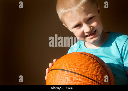 Beautiful happy little child (boy) with basketball, close up horizontal portrait with copy space - Stock Photo
