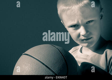 Upset little child (boy) with basketball, close up horizontal portrait with copy space - Stock Photo
