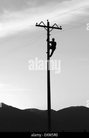 Silhouette of a lineman working on a telephone pole, Stevensville, Montana - Stock Photo