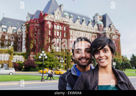 A young Indian ethnicity couple poses in front of the Fairmont Empress Hotel; Victoria, Vancouver Island, British - Stock Photo