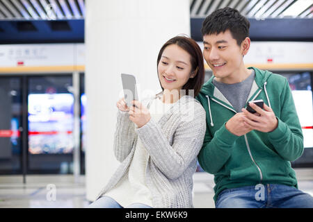 Young couple using smart phone at subway station - Stock Photo