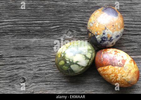 Three Colored Easter Eggs On Vintage Country Board