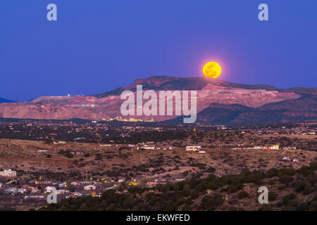 The March 5, 2015 mini-moon rises over the Santa Rita Copper Mine and cliff formation known locally as the Kneeling - Stock Photo
