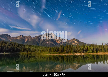 Star trails over Patricia Lake and Pyramid Mountain in Jasper National Park, Alberta, Canada. Moonlight provides - Stock Photo