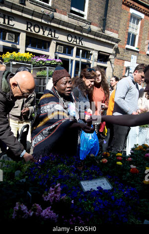 Columbia Road Sunday flower market, Spring 2015. Customers choose plants in front of the Royal Oak pub. - Stock Photo