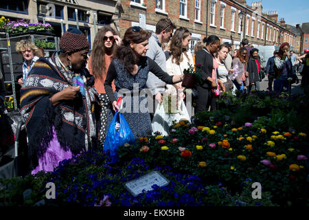 Columbia Road Sunday flower market, Spring 2015. Customers choose plants. - Stock Photo