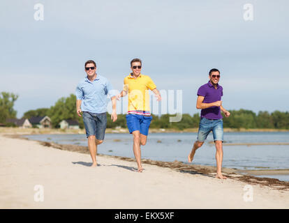 smiling friends in sunglasses running along beach - Stock Photo