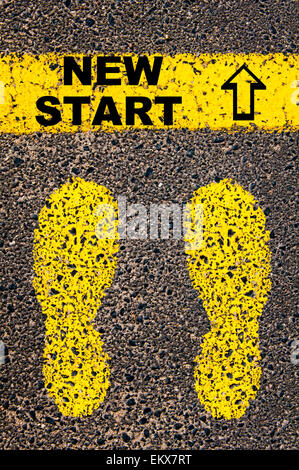 New Start message. Conceptual image with yellow paint footsteps on the road in front of horizontal line over asphalt - Stock Photo