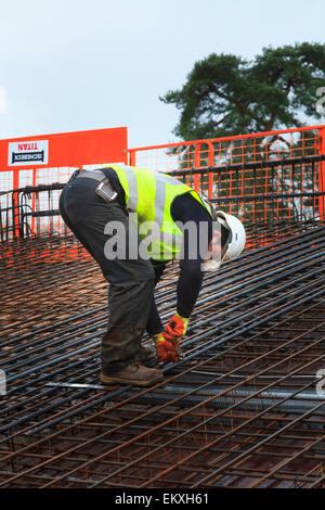 Construction worker tying up reinforcing bars prior to pouring of concrete on a commercial building roof. - Stock Photo