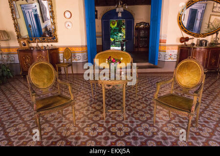 Cuba Trinidad typical Cuban home sitting room antique mirrors sideboards  chairs ornate walls & tile tiles - Cuba Trinidad Typical Cuban Home Sitting Room Antique Chairs Stock