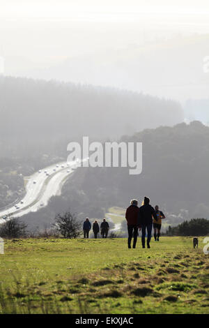 People walking on South Down at Butser hill in silhouette with A3 trunk road - Stock Photo