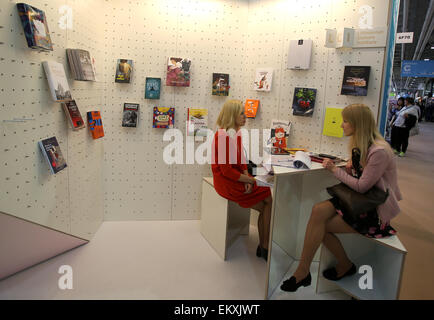 London,  UK. 14th Apr, 2015. An exhibitor (L) communicates with a visitor at the London Book Fair in Olympia, London, - Stock Photo