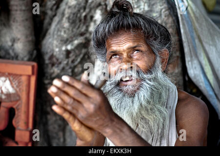 A Holy Man Sits Looking Upwards With Hands Raised; Haridwar India - Stock Photo