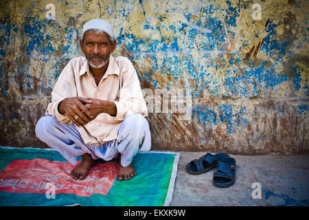 A Barefoot Man Crouches On A Blanket On The Side Of The Street; Delhi India - Stock Photo