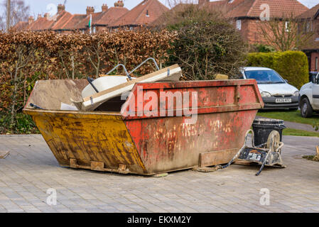Household waste in a skip dumpster on a residential driveway during a home renovation project - Stock Photo