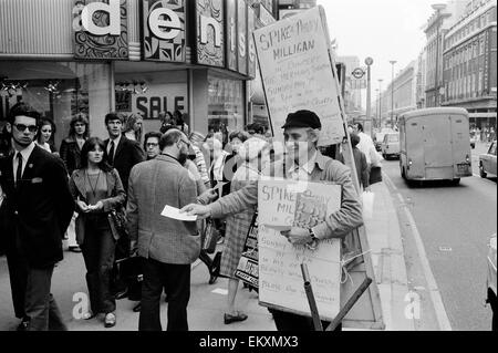Spike Milligan & wife Paddy use a Sandwich board - borrowed from British Rail Lost Property - to advertise their - Stock Photo