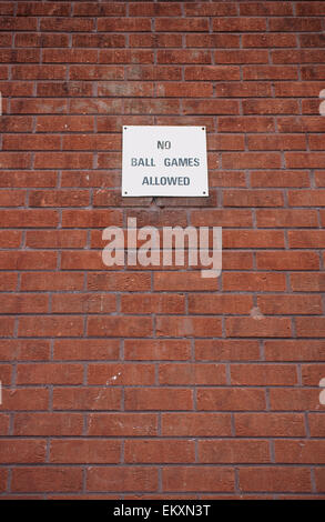 No ball games sign against a brick wall in a residential area to prevent anti-social activities - Stock Photo