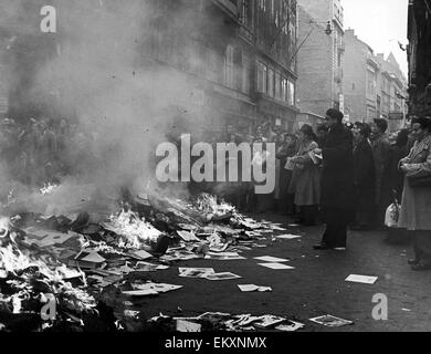 A crowd of Hungarians watch books and pamphlets from a ransacked Russian bookshop being burnt in a Budapest street. - Stock Photo