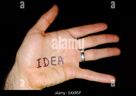 Idea written on a white man's hand photographed against a black background. - Stock Photo