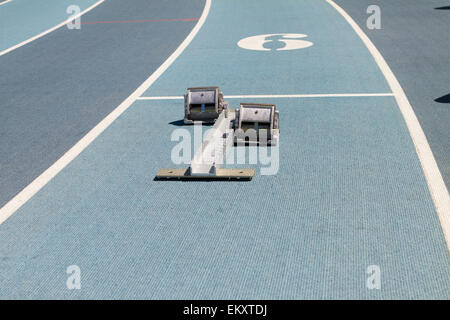 Blue mondo surface running track lanes with starting blocks - Stock Photo
