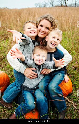 Mother holding three boys in her arms - Stock Photo