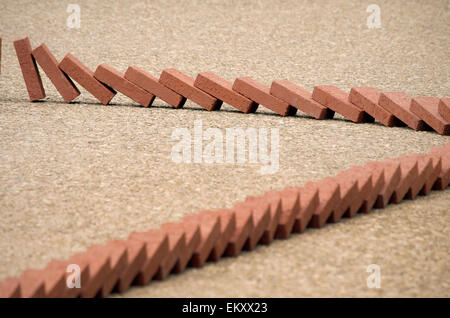 Bricks tumble and topple one after the other, the domino effect, or domino theory. - Stock Photo