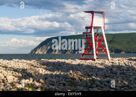 a lifeguard chair on rocky ingonish beach with cape smokey in the background in the