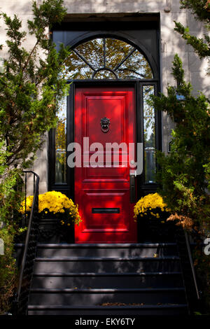Windows and red door framed by potted flowers and green shrubs; Montreal, Quebec, Canada - Stock Photo