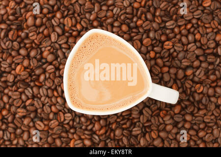 Cup of coffee with milk on coffee beans background - Stock Photo