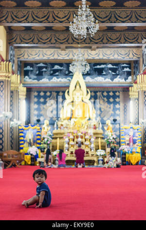 Thailand, Chiang Mai, Baby sitting alone on red carpet of temple - Stock Photo