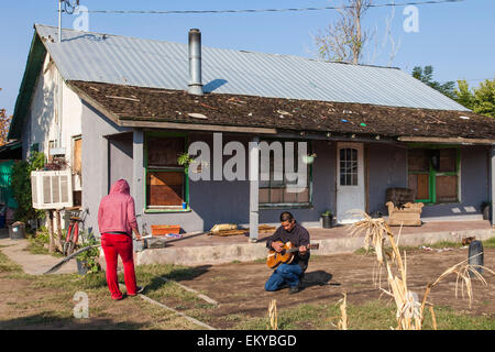 Couple in their front yard in East Porterville, CA.While their well is still working, their next door neighbor's - Stock Photo