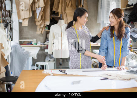 Two female fashion designers talking in studio - Stock Photo