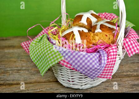 Easter hot cross buns in white wicker basket with gingham fabric. - Stock Photo